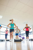 Instructor with fitness class performing step aerobics exercise Stock Images