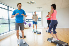 Instructor with fitness class performing step aerobics exercise Stock Image