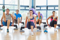 Instructor with fitness class performing step aerobics exercise Royalty Free Stock Photo