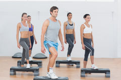 Instructor with fitness class performing step aerobics exercise Royalty Free Stock Images