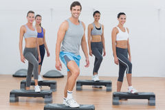 Instructor with fitness class performing step aerobics exercise Stock Photos