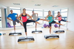 Instructor with fitness class performing step aerobics exercise Royalty Free Stock Photos