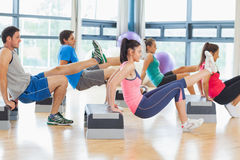 Instructor with fitness class performing step aerobics exercise. Full length side view of instructor with fitness class performing step aerobics exercise in gym Royalty Free Stock Photography