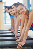 Instructor with fitness class performing step aerobics exercise Royalty Free Stock Image