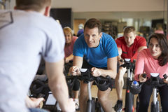 Instructor in foreground with spinning class at a gym Royalty Free Stock Images