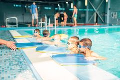 Instructor gives child plank for swimming. Children in water with goggles are going to do swim exercise. Healthy activity in pool. Sportive kids activity in royalty free stock photos