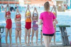 Instructor and group of children doing exercises near a swimming pool.  royalty free stock photo