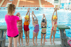 Instructor and group of children doing exercises near a swimming pool.  stock photography
