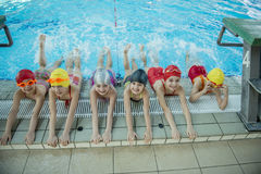 Instructor and group of children doing exercises near a swimming pool Royalty Free Stock Photography