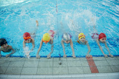 Instructor and group of children doing exercises near a swimming pool Royalty Free Stock Image