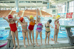 Instructor and group of children doing exercises near a swimming pool Royalty Free Stock Images