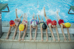 Instructor and group of children doing exercises near a swimming pool Stock Photography