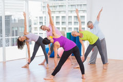 Instructor guiding friends in stretching exercise Stock Image