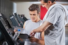 Instructor Guiding Man To Fill The Membership Form Stock Images
