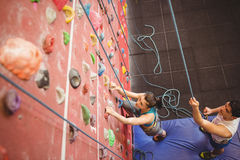 Instructor guiding woman on rock climbing wall Stock Images
