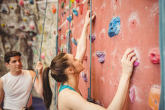 Instructor guiding woman on rock climbing wall royalty free stock photography