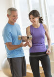 Instructor Guiding Woman In Weightlifting Royalty Free Stock Images
