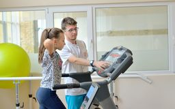 Instructor in gym with little girl. On treadmill stock images