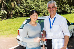 Instructor handing driving license Royalty Free Stock Photo