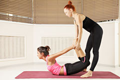 Instructor helping in back bend pose Stock Photo