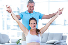 Instructor helping exercising pregnant woman. Instructor helping exercising pregnant women at home Stock Images