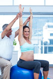 Instructor helping pregnant woman in exercising. Instructor helping pregnant women in exercising at gym Royalty Free Stock Photos