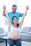 Instructor helping pregnant woman. Instructor helping pregnant women at home Stock Photography