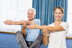 Instructor helping senior man with sport exercises Royalty Free Stock Photography