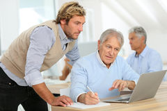 Instructor helping senior man in training. Senior men attending business class with trainer Royalty Free Stock Photos