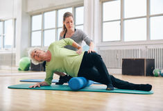 Instructor helping senior woman for a myofascial release techniq. Female instructor helping senior women using a foam roller for a myofascial release massage at stock photo