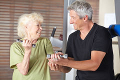Instructor helping senior woman in rehab gym Royalty Free Stock Images