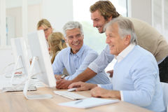 Instructor helping seniors in informatics Royalty Free Stock Image