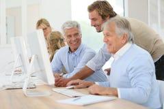 Instructor helping seniors in informatics. Instructor helping senior men with computing class Royalty Free Stock Image