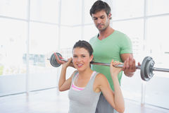 Instructor helping woman to lift barbell in gym Stock Images
