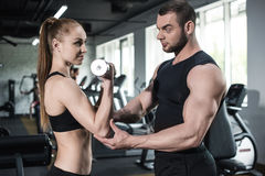 Instructor helping young smiling woman with dumbbell Royalty Free Stock Photography