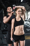 Instructor helping young smiling woman with dumbbell Stock Images