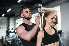 Instructor helping young smiling woman with dumbbell Royalty Free Stock Image