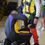 Instructor Helps Apprentice del Skydiver para atar la correa de la seguridad en su traje del paracaidista Imagenes de archivo