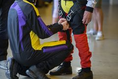 Instructor Helps Apprentice del Skydiver para atar la correa de la seguridad en su traje del paracaidista Imagen de archivo libre de regalías