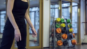 Instructor helps athlete to do exercises in fitness center. Hot trainer in black skinny pants, T-shirt helping to work out in sport studio. Exercise on stock video