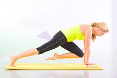 Instructor hermoso de los pilates con la estera amarilla de la yoga Foto de archivo