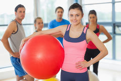 Instructor holding exercise ball with fitness class in background Stock Image