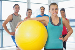 Instructor holding exercise ball with fitness class in background Stock Photos