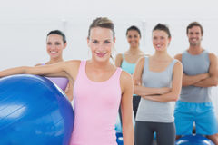 Instructor holding exercise ball with fitness class in background Stock Photo