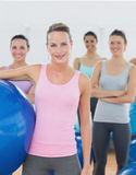 Instructor holding exercise ball with fitness class in background Royalty Free Stock Image