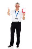 Instructor holding L sign. Portrait of professional senior driving instructor holding L sign stock images