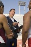 Instructor Instructing Male Athletes foto de archivo libre de regalías