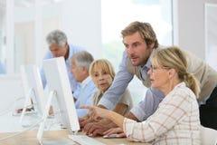 Instructor joven que ayuda a mayores en clase computacional Imagen de archivo libre de regalías