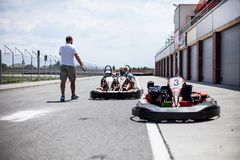 The instructor of the kart track conducts the instruction before the race. Pair karting. Father and son in the summer active royalty free stock photo
