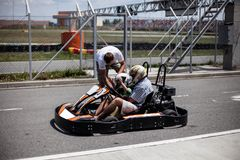 The instructor of the kart track helps the boy to fasten his helmet. Pair karting. Father and son in the summer active family royalty free stock images
